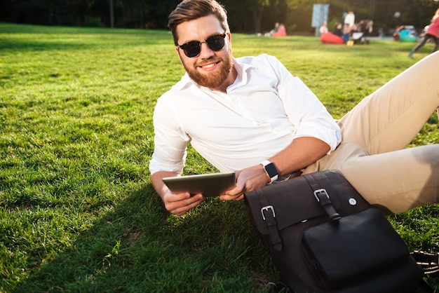 Smiling bearded man in sunglasses lying on grass outdoors with tablet computer and looking at the camera
