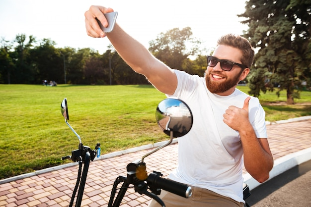 Smiling bearded man in sunglasses sitting on modern motorbike outdoors and making selfie on his smartphone