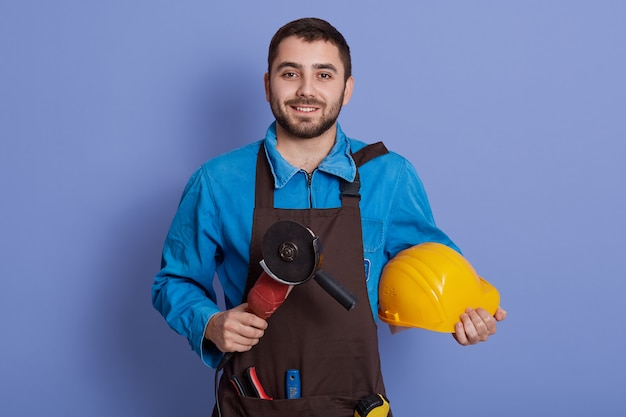 Smiling bearded man wearing brown apron holding grinder tool and yellow protective helmet in hands