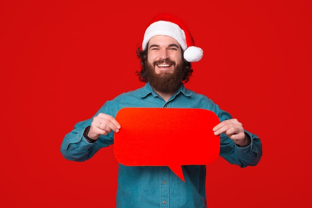 Smiling bearded man wearing christmas hat holds a speech bubble over red background