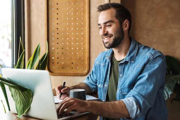 Smiling bearded man wearing denim shirt writing and typing on laptop while working in cafe indoors