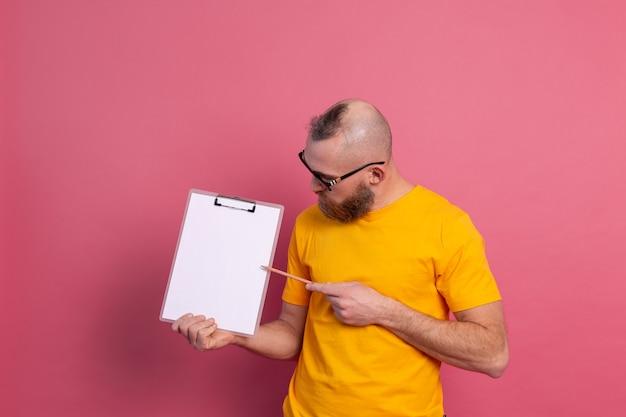 白紙のポインティングでクリップボードを保持しているカジュアルな服を着て眼鏡をかけて笑顔のひげを生やした男