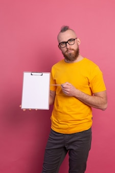 Smiling bearded man wearing eyeglasses wearing casual clothes holding a clipboard with a blank paper pointing