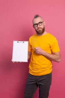 Sorridente uomo barbuto che indossa occhiali da vista che indossano abiti casual in possesso di un blocco per appunti con una carta bianca che punta