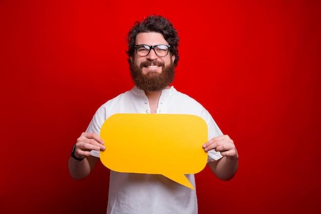 안경을 쓰고 웃는 수염 남자는 빨간색에 노란색 거품 연설을 잡고있다