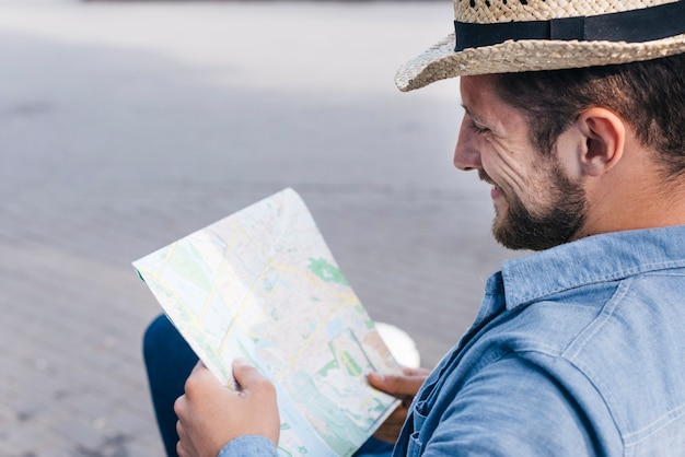 Smiling bearded man wearing hat reading map at outdoors