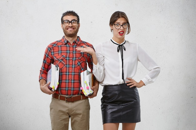 Smiling bearded man wears big spectacles, holds piles of books, stands next to beautiful woman who gestures unhappily
