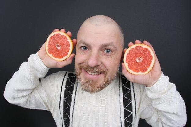 彼の手にカットグレープフルーツとひげを生やした男の笑顔