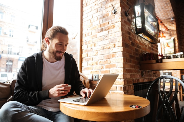 Uomo barbuto sorridente con il computer portatile in caffè
