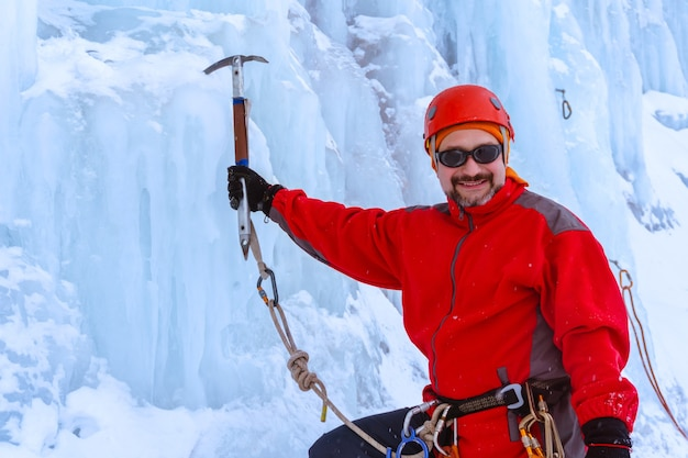 Smiling bearded mountaineer with ice ax on blue glacier background