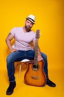 앉아 어쿠스틱 기타를 들고 수염 된 음악가 남자 미소