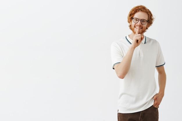 眼鏡をかけて白い壁にポーズをとって笑顔のひげを生やした赤毛の男