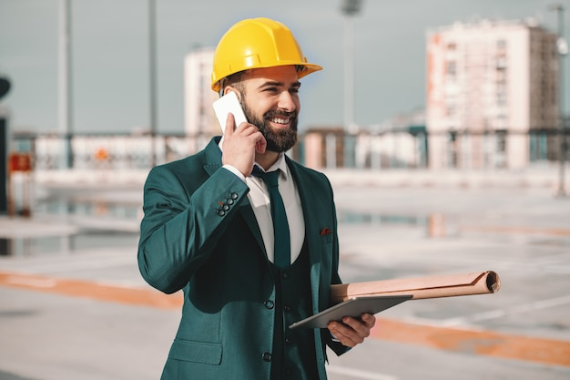Smiling bearded successful architect in formal wear and helmet on head using smart phone. under armpit blueprints and in hand tablet. sometimes later becomes never, do it now.