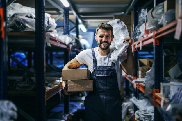 수입 및 수출 회사의 창고에서 걷는 동안 상자와 가방을 들고 이동하는 작업 바지에 수염을 기른 문신을 한 근면 한 블루 칼라 노동자를 웃고 있습니다.