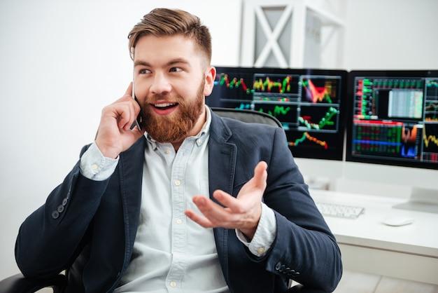웃고 있는 수염난 젊은 사업가가 사무실에 앉아 휴대폰 통화를 하고 있다