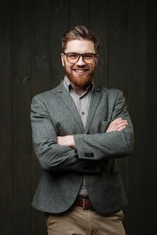 Улыбающийся бородатый молодой бизнесмен, сложив руки, изолирован на черном деревянном фоне