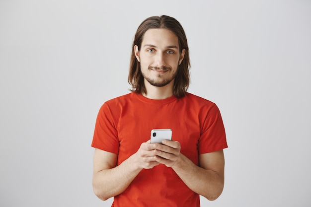 Smiling bearded young guy using mobile phone