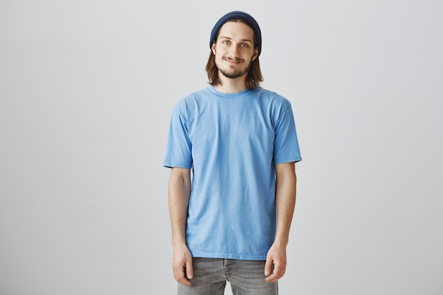 Smiling bearded young man in blue t-shirt and beanie looking enthusiastic