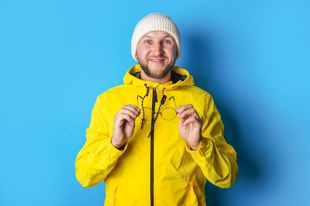 青い背景の上の黄色いジャケットで眼鏡を保持しているひげを生やした若い男に笑みを浮かべてください。