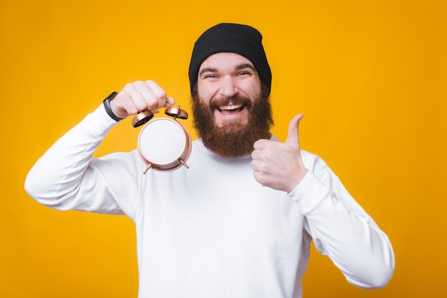 Smiling bearded young man is holding an watch and showing thumb up gesture near yellow wall.