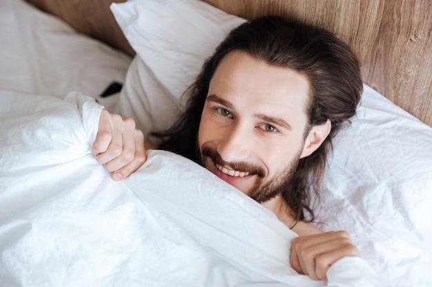 Giovane barbuto sorridente che si trova a letto