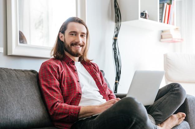 Улыбающийся бородатый молодой человек сидит на диване и с помощью ноутбука