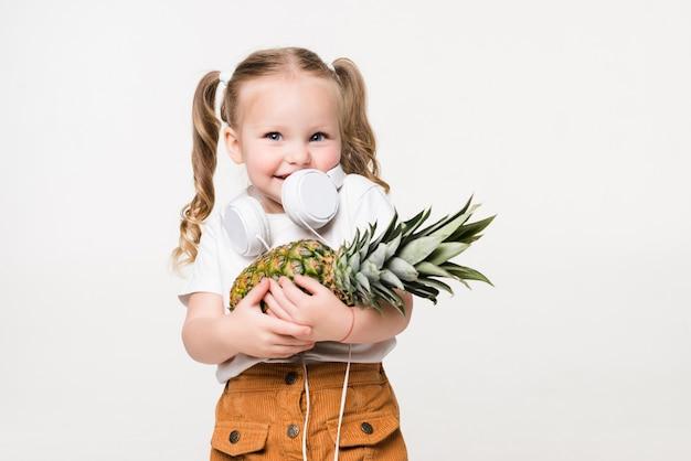 Smiling beatiful little girl holding pineapple