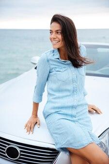 彼女の高価な車のそばに立っている美しい女性の笑顔