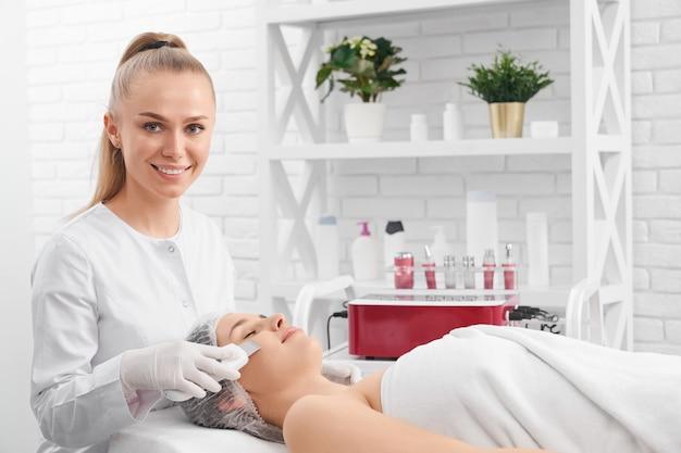 Улыбающийся косметолог делает косметическую процедуру для пациента