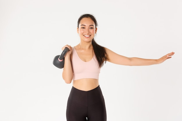 Smiling beautiful asian fitness girl, gym coach extend one hand and lift kettlebell, bodybuilding, gaining muscle strength, standing white background.