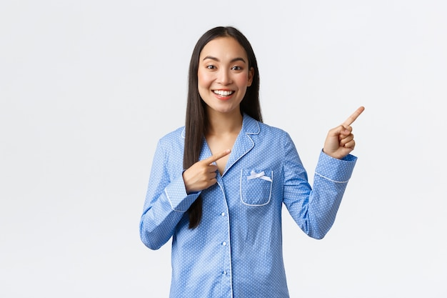 Smiling beautiful asian girl in blue pajamas making announcement, pointing fingers upper right corner to show big news or promo banner, recommend advertisement over white wall