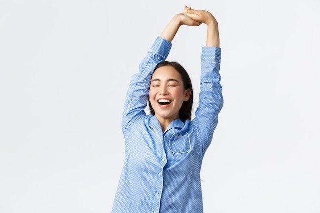 Smiling beautiful asian girl in pajamas stretching with satisfied face, yawning with closed eyes, had good sleep or nap, waking-up morning. woman in jammies enjoying morning routine