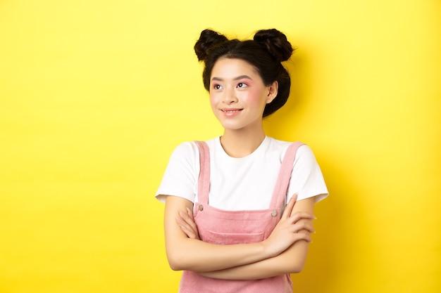 グラマーメイクで美しいアジアの女の子を笑顔、幸せそうな顔でロゴを脇に見て、黄色の夏服に立っています。