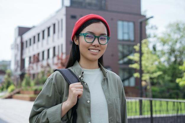 ストリート旅行のコンセプトでカメラを見てバックパックを保持している美しいアジアの観光客の笑顔