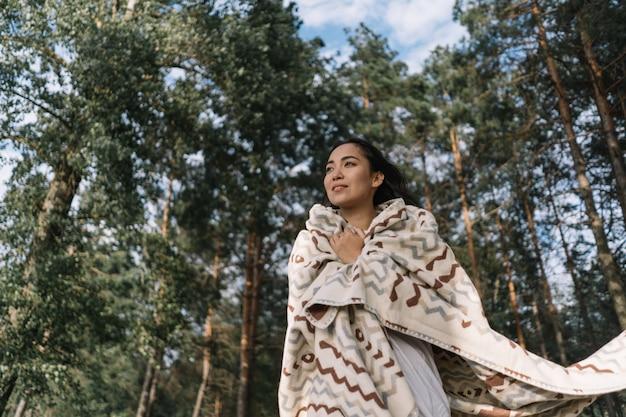 Smiling beautiful asian woman breathing fresh air in green park, thinking, enjoying landscapes