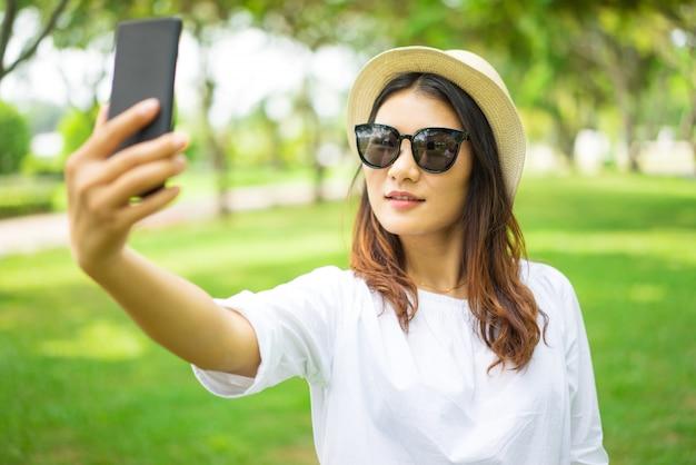夏の公園でセルフをしているサングラスで美しいアジアの女性を笑顔にする。