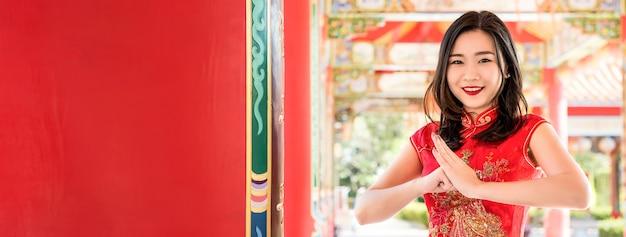 伝統的な赤い中国のcheongsamドレスで敬礼を作って美しいアジアの女性を笑顔