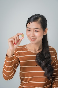 Smiling beautiful asian woman looking at coin