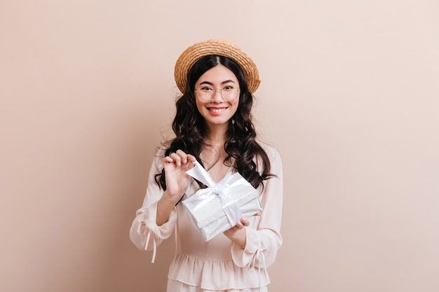 Smiling beautiful asian woman opening birthday present. front view of happy japanese woman with gift wearing straw hat.