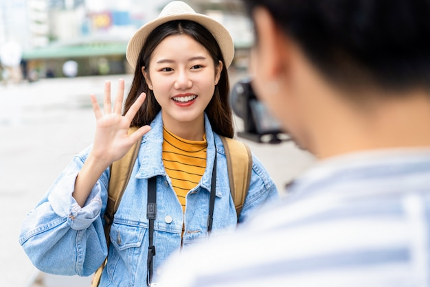 Smiling beautiful asian woman say hi gesture with hand