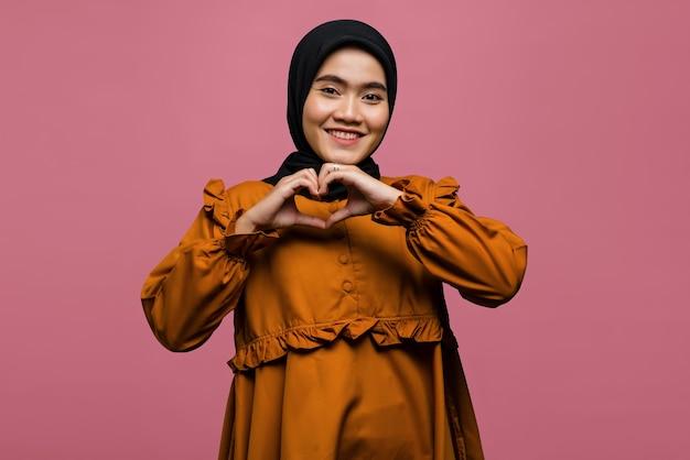 愛のサインを示す笑顔の美しいアジアの女性