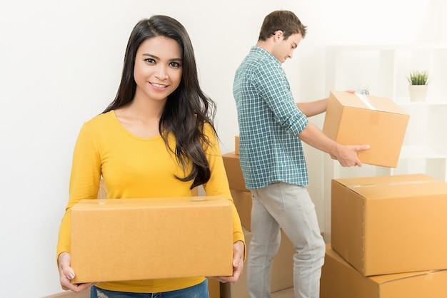 Smiling beautiful asian woman with her partner moving stuff into new house