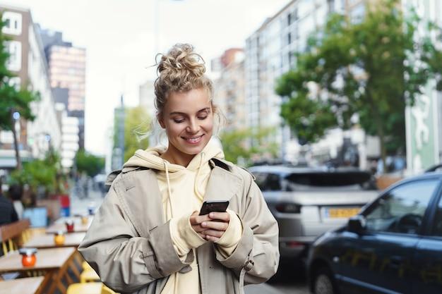 휴대 전화를 사용 하여 웃는 아름 다운 금발 소녀.