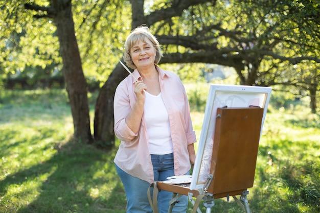 明るい晴れた日に公園のイーゼルに絵を描きながら、笑顔の美しい金髪の成熟した 60 歳の白人女性アーティスト。