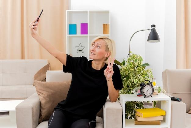Sorridente bella bionda donna russa si siede sulla poltrona gesticolando mano segno di vittoria guardando il telefono prendendo selfie all'interno del soggiorno
