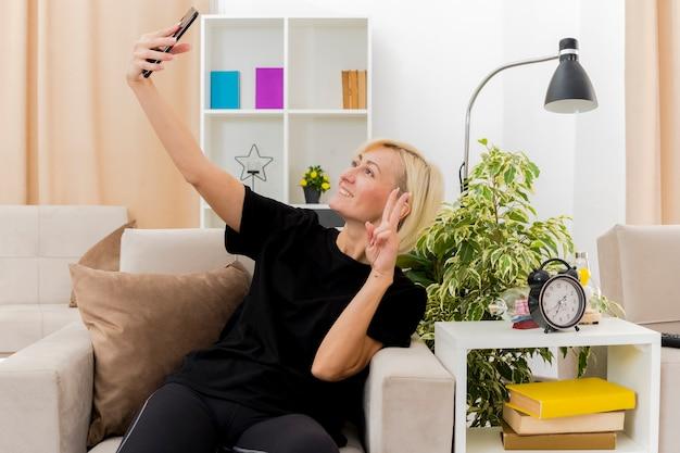 Sorridente bella bionda donna russa si siede sulla poltrona gesticolando mano segno di vittoria guardando il telefono