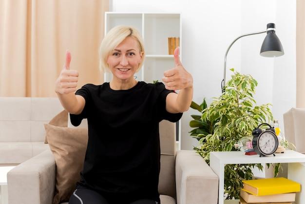 La bella donna russa bionda sorridente si siede sui pollici in su della poltrona con due mani