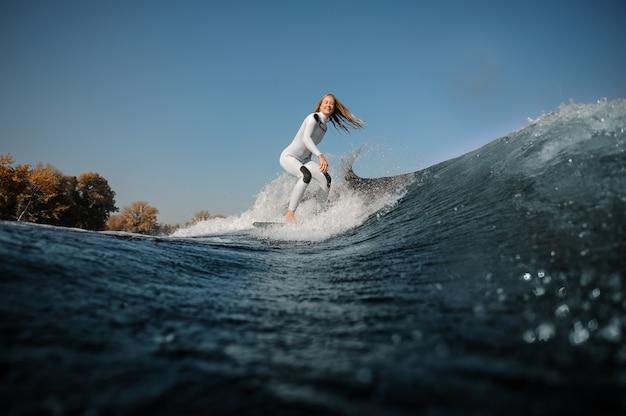 Улыбающаяся красивая блондинка в белом купальнике катается на вейкборде на согнутых коленях