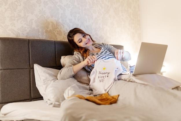 ノートパソコンを介してビデオ通話を持つ美しいブルネットの笑みを浮かべてください。彼女が買ったベビー服を見せている女性。イブニングタイム。