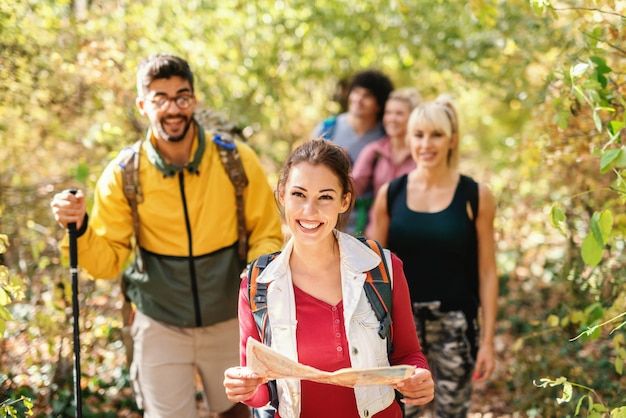 Smiling beautiful brunette holding map and leading the rest of hikers through woods in autumn.